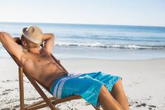 Handsome man sleeping on his deck chair - stock photo