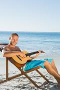 Cheerful handsome man strumming guitar Stock Photos