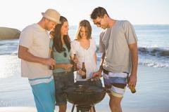 Stock Photo of Cheerful young friends having barbecue together