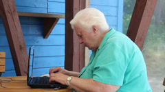 Old woman happy to solve the problem with using her laptop computer. Stock Footage