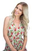 Cheerful attractive blonde wearing flowered dress posing - stock photo