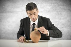 Businessman putting coin into the piggy bank Stock Photos