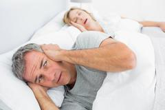 Fed up man blocking his ears from noise of wife snoring - stock photo