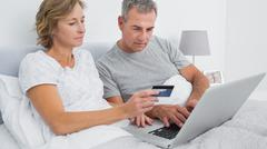 Thoughtful couple using their laptop to buy online - stock photo