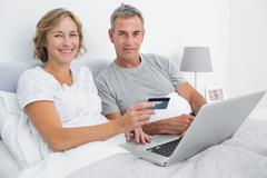 Smiling couple using their laptop to buy online - stock photo