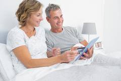 Cheerful couple using their tablet pc to buy online - stock photo