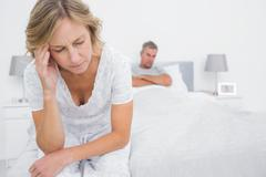 Upset couple sitting on opposite ends of bed after a fight - stock photo
