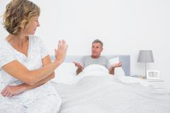 Stock Photo of Annoyed woman looking at husband gesturing during a fight