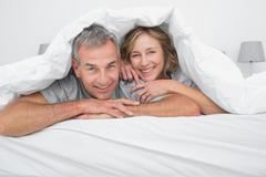 Stock Photo of Cheerful couple under the duvet