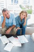 Stock Photo of Anxious couple sitting on their couch paying their bills