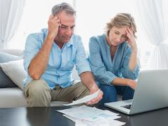 Worried couple paying their bills online with laptop - stock photo