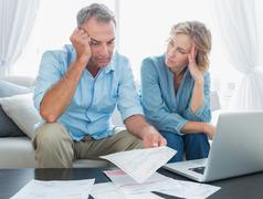Worried couple using their laptop to pay their bills Stock Photos