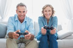 Stock Photo of Happy couple playing video games together on the couch