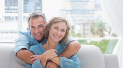 Stock Photo of Content man hugging his wife on the couch