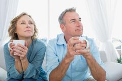 Stock Photo of Thoughtful middle aged couple sitting on the couch having coffee
