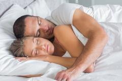Cute couple sleeping and cuddling in bed Stock Photos