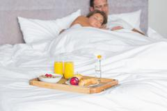 Cuddling couple asleep with breakfast tray on bed - stock photo