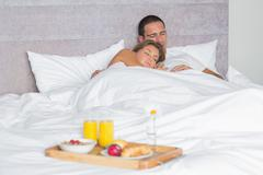 Attractive couple sleeping with breakfast tray on bed Stock Photos