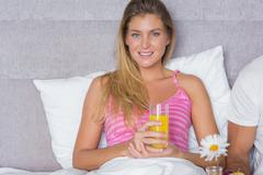 Stock Photo of Smiling young woman having breakfast in bed with partner