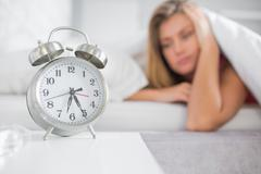 Tired blonde staring at her alarm clock - stock photo