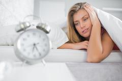 Exhausted blonde staring at her alarm clock - stock photo