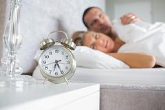 Exhausted couple looking at alarm clock - stock photo