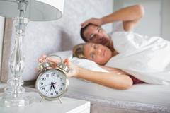 Tired couple looking at alarm clock in the morning with woman turning it off Stock Photos