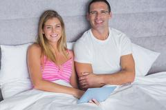 Cute couple using their tablet pc together in bed - stock photo