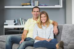 Stock Photo of Attractive young couple sitting on their couch