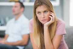 Sad woman thinking on couch after fight with husband Stock Photos