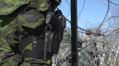 Military, soldier sidearm and razer wire Stock Footage
