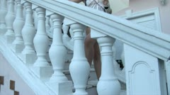 Model standing on the stairs and posing with umbrella in her hand Stock Footage