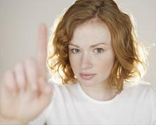Redhead holding up one finger - stock photo