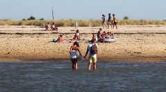 Hand in hand couple crossing low tide   Stock Footage