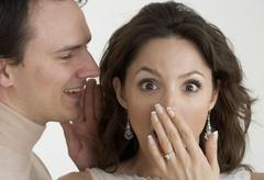 Man telling woman a surprising secret - stock photo