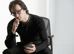 Professional man sitting thoughtfully Stock Photos