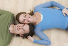 Smiling couple lying on wood floor Stock Photos