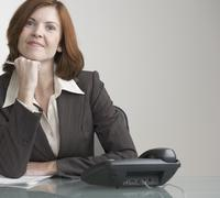 Attractive businesswoman with phone at desk Stock Photos