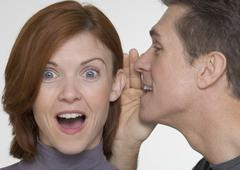 Man telling woman surprising secret - stock photo