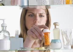Woman removing medicine from cabinet - stock photo