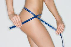 Nude female measuring her waist - stock photo