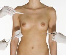 Nude female torso with medical instruments - stock photo