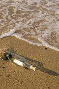 Message in a bottle on beach - stock photo