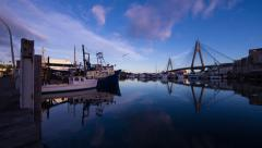 Fishing Trawlers moored next to modern bridge at sunrise 241GYDH1 NTSC Stock Footage