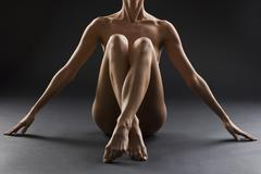 Nude female with legs crossed - stock photo