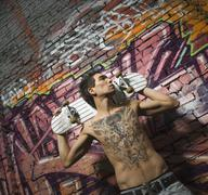 Asian man holding skate board in front of graffitied wall - stock photo