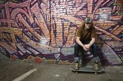 Young man with skateboard in front of graffitied wall - stock photo
