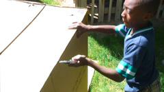 Boy using small saw to cut a cardboard box Stock Footage