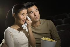 Couple watching a sad movie - stock photo