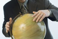 Man spinning a globe Stock Photos